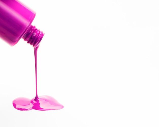 Primer plano de esmalte de uñas rosa derramando fuera de botellas