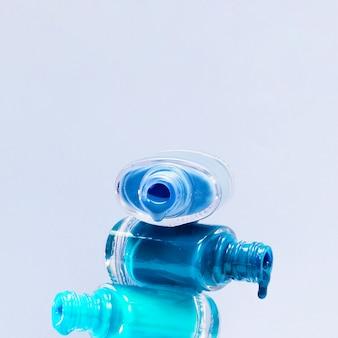 Primer plano de esmalte de uñas de tonos azules con botella abierta apilada