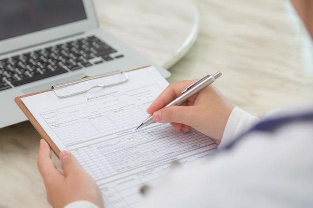 Primer plano de especialista rellenando un formulario
