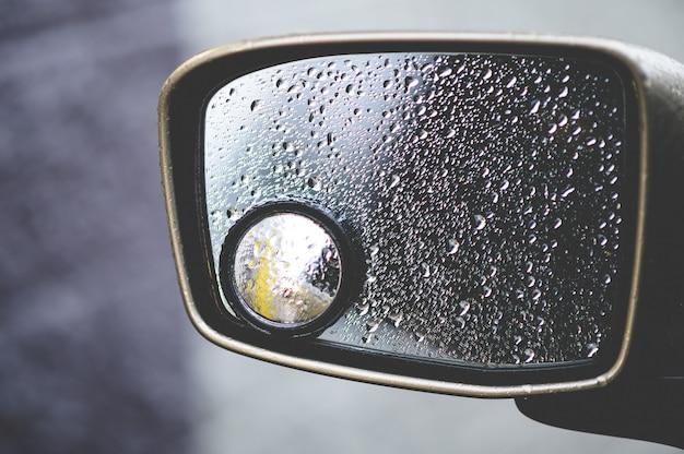 Primer plano de un espejo retrovisor cubierto de gotas de lluvia bajo la luz del sol
