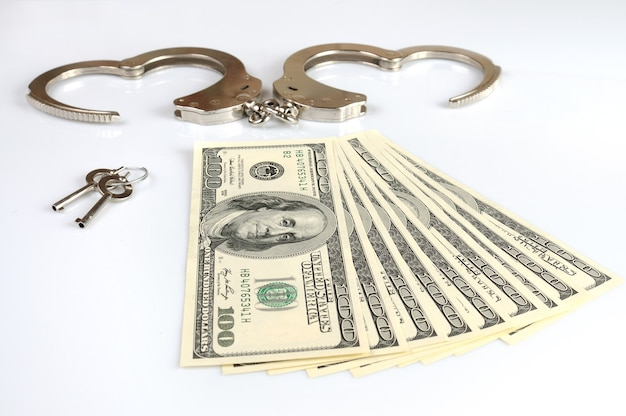 Primer plano de esposas metálicas abiertas, llaves y pila de dólares estadounidenses en efectivo aislado sobre fondo blanco. ganancia ilegal de dinero, soborno, serie de corrupción