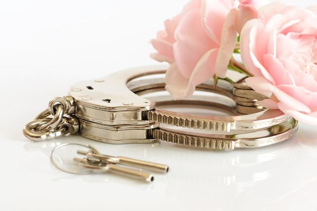 Primer plano de esposas metálicas, llaves y flor rosa romántica