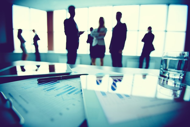 Primer plano de estadísticas con empleados de fondo