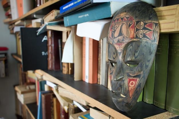 Primer plano de una estantería con libros y una máscara antigua en un pequeño apartamento en los suburbios de parís