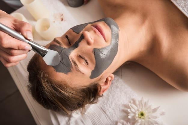 Primer plano de una esteticista aplicar mascarilla en la cara de la mujer