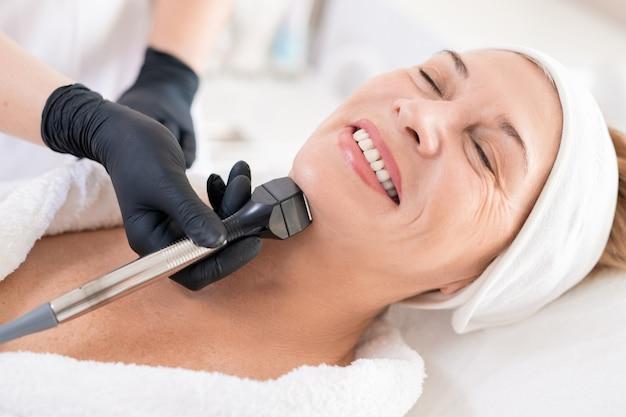 Primer plano de esteticista irreconocible en guantes de látex exfoliante piel de mujer madura sonriente con dispositivo mecánico de limpieza