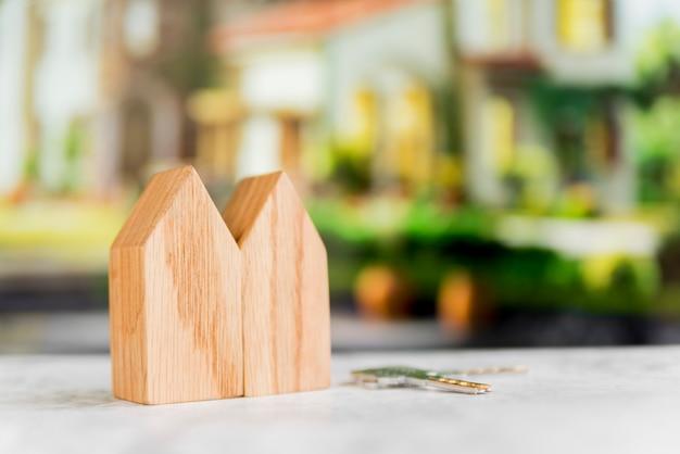 Primer plano de la estructura de la casa de madera con llaves en la superficie contra el fondo borroso