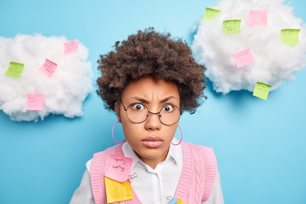 Primer plano de un estudiante afroamericano desconcertado que se ve sorprendido por la cámara usa gafas redondas toma notas en las pegatinas tiene diferentes tareas que hacer aisladas sobre una pared azul