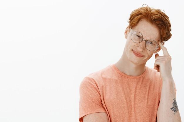 Primer plano de estudiante inteligente y atractivo, hombre de gafas apuntando a la cabeza, dando pistas para pensar