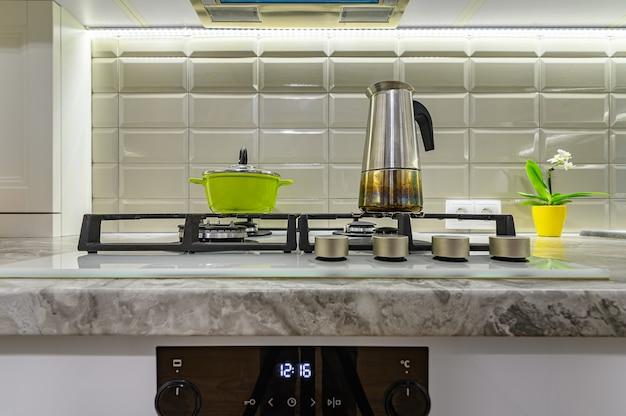 Primer plano de la estufa en blanco acogedor y cómodo interior de cocina clásica contemporánea con muebles de madera, vista frontal