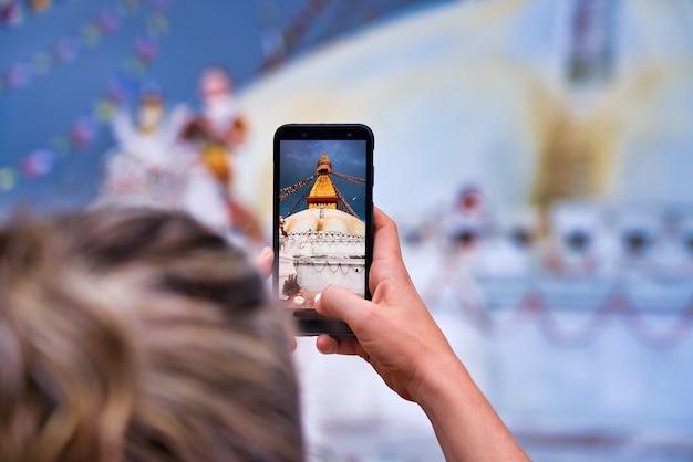Primer plano de la estupa de boudhanath en katmandú. la foto tomada por una mujer occidental desde atrás. rubia con el pelo recogido. tomar fotos con un teléfono inteligente. bokeh