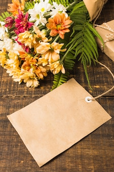 Primer plano de etiqueta en blanco cerca de ramo de flores frescas