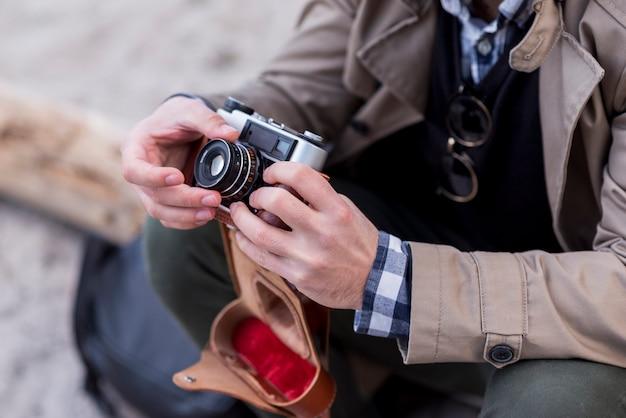 Primer plano de un excursionista hombre ajustando la cámara