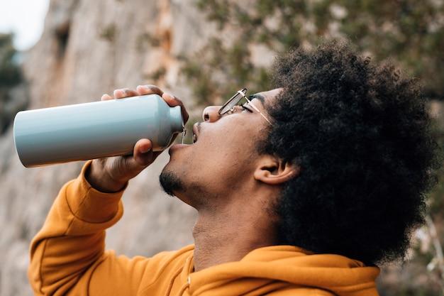 Primer plano de un excursionista masculino bebiendo el agua de la botella