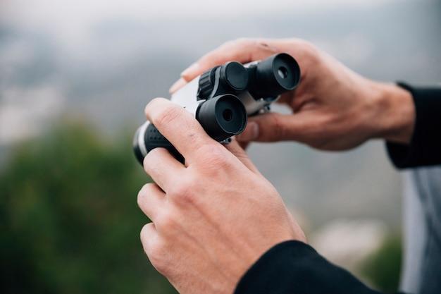 Primer plano de un excursionista masculino con binoculares en la mano