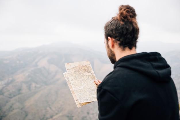 Primer plano de un excursionista masculino leyendo el mapa