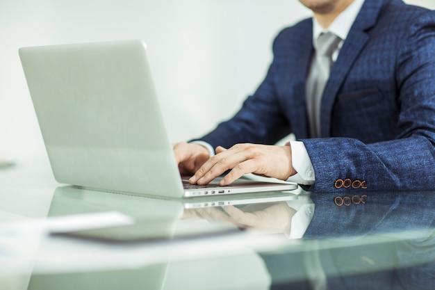 Primer plano - un exitoso hombre de negocios que trabaja en la computadora portátil en el lugar de trabajo