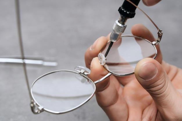 Primer plano de la fabricación de gafas médicas con herramienta de oftalmología en la oficina de la clínica
