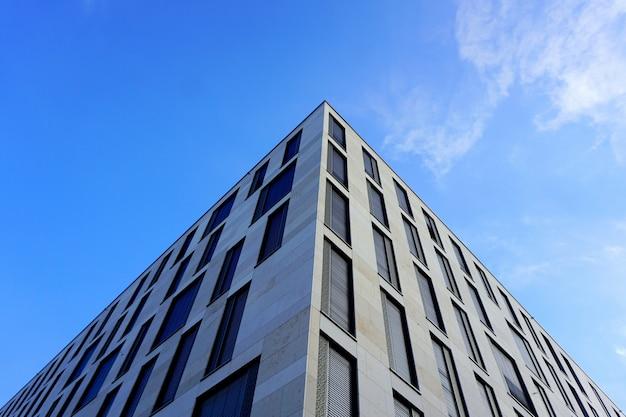 Primer plano de la fachada de un edificio moderno contra el cielo azul.