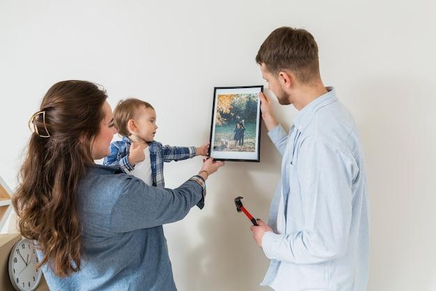 Primer plano de la familia feliz con marco de foto contra la pared en el nuevo hogar
