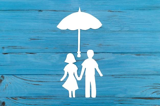 Primer plano de la familia de papel feliz sobre fondo azul