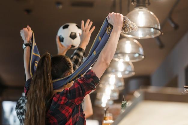 Primer plano de fanáticos del fútbol que animan celebrando la victoria