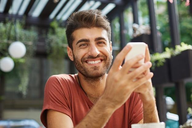 Primer plano de feliz apuesto joven sonriendo mientras está sentado en la cafetería al aire libre y mediante teléfono móvil