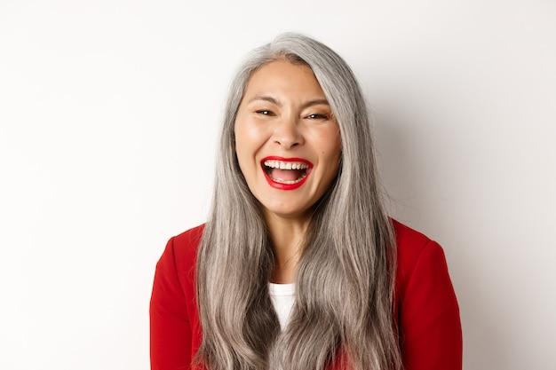 Primer plano de feliz empresaria asiática con largo cabello gris, vestido con chaqueta roja, riendo y sonriendo con alegría a la cámara, fondo blanco.
