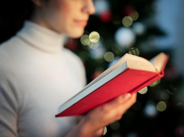 Primer plano femenino leyendo libro de cuentos de navidad