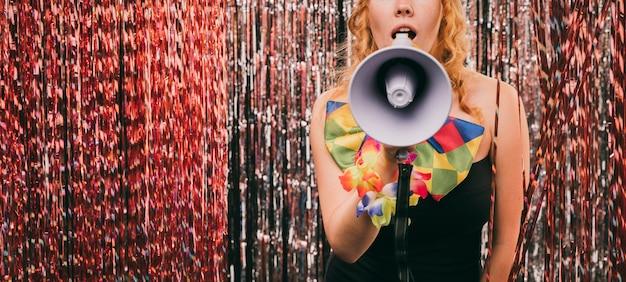 Primer plano femenino con megáfono en fiesta de carnaval