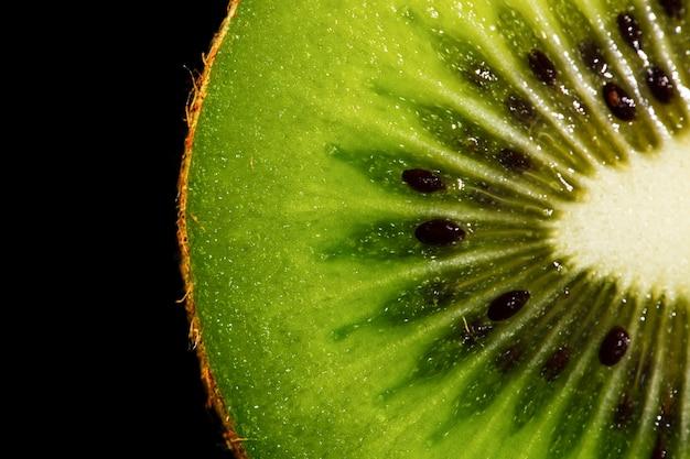 Primer plano de fibras verdes y granos negros de kiwi fresco