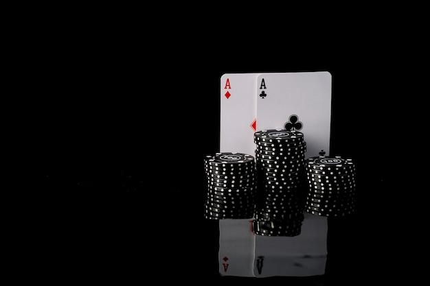 Primer plano de fichas de póquer negro y dos ases jugando a las cartas