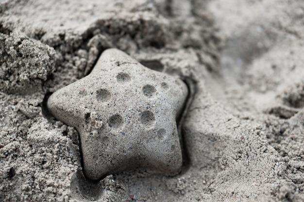 Primer plano de una figura parecida a una estrella de mar hecha con arena húmeda