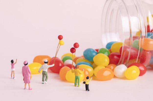 Primer plano de figuras de personas con globos y caramelos de colores - concepto del día del niño