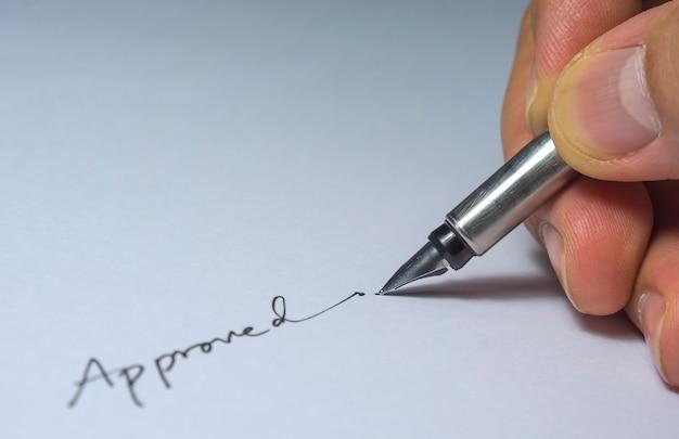 Primer plano de la firma aprobada con los dedos y la pluma, bombilla desde el lado izquierdo