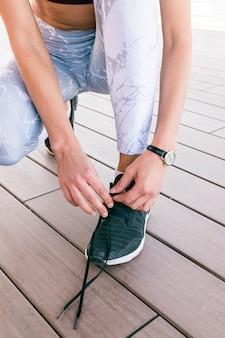 Primer plano de fitness joven atar cordones de los zapatos en cuclillas en piso de madera dura