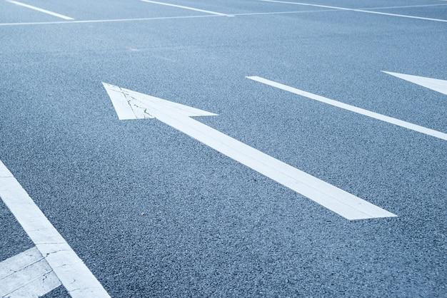 Primer plano de flecha pintada en el asfalto