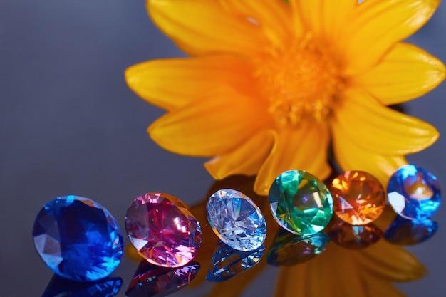 Primer plano de flor de naranja y varios cristales elegantes en una superficie de espejo negro profundo, brillan y brillan