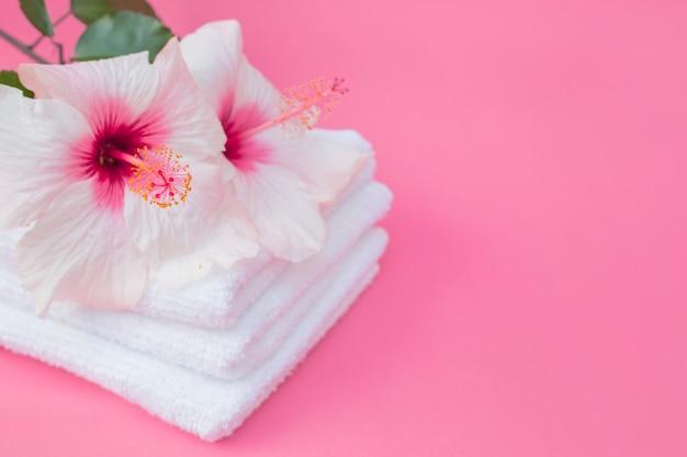 Primer plano de flores de hibisco y toalla blanca sobre fondo rosa