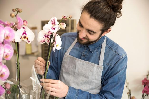 Primer plano de un florista masculino arreglando la flor de la orquídea
