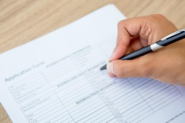 Primer plano de formulario de solicitud llenado mano femenina