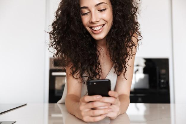 Primer plano de la foto de una hermosa mujer caucásica de 20 años con cabello castaño rizado con ropa de ocio de seda sonriendo con dientes perfectos y mirando el teléfono celular negro en las manos