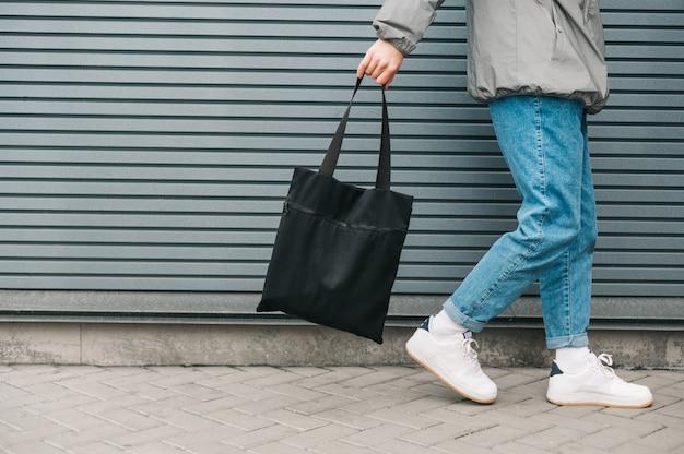 Primer plano, foto recortada, el hombre con ropa elegante va sobre un fondo de una pared gris con una bolsa ecológica en una bolsa negra en la mano
