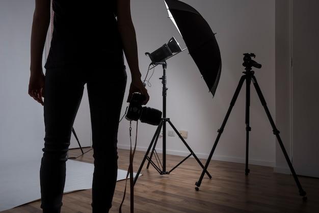 Primer plano de un fotógrafo mujer sosteniendo la cámara en estudio fotográfico