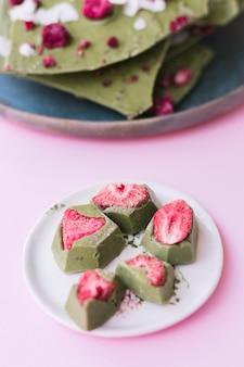 Primer plano de fresa con postre de chocolate verde en un plato blanco sobre una superficie rosada