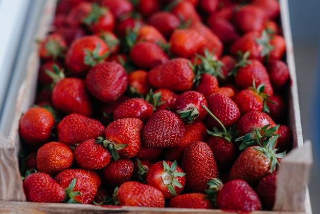 Primer plano de fresas frescas maduras en un contenedor para la venta. dieta saludable.