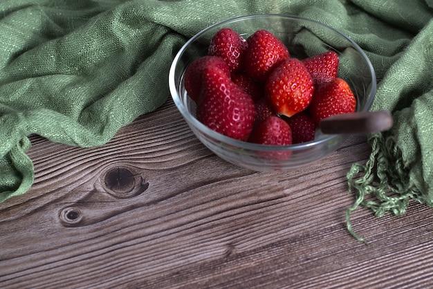 Primer plano de fresas frescas en un recipiente de vidrio y un textil verde sobre una superficie de madera