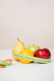 Primer plano de frutas frescas con cinta métrica en la mesa