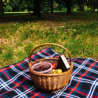 Primer plano de frutas y libro en la cesta de mimbre en manta