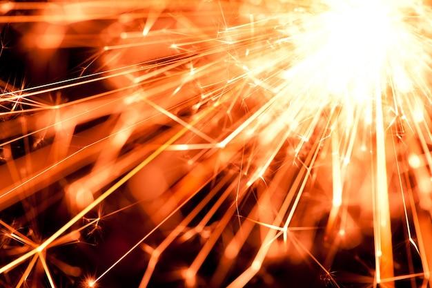 Primer plano de un fuego de color naranja brillante de una bengala ardiente arde en la oscuridad